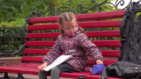 pigtail : Girl child with glasses A girl sits on a park bench. Autumn day.