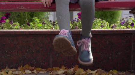 after school : Girl child sits on a bench and her legs. Close-up of childs feet. Autumn day.