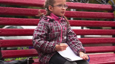 vurgulayıcı : Girl child with glasses A girl sits on a park bench. Autumn day.
