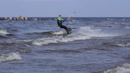 kitesurfer : A male kite surfer rolls on the surface of the water.