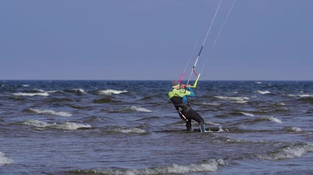 kitesurfer : SLOW MOTION: A male kite surfer enters the water and starts moving. The kite surfer.
