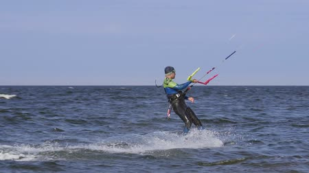 skok : A male kite surfer rolls on the surface of the water.