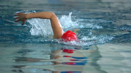 plavec : SLOW MOTION: Female athlete swimming in crawl style. Splashes of water scatter in different directions.