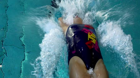 sztafeta : SLOW MOTION: Female athlete swims on his back under water. Start of the sports swim.