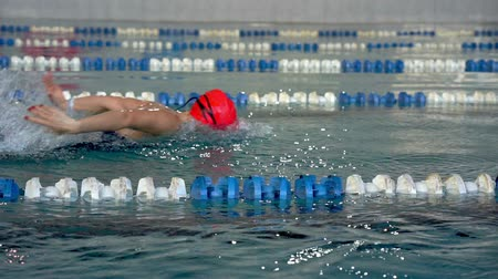 binnenzwembad : SLOW MOTION: Female athlete swimming in crawl style. Splashes of water scatter in different directions.