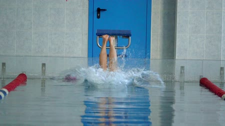relevos : SLOW MOTION: Woman athlete beautifully jumps into the pool water. Start of the sports swim. Archivo de Video