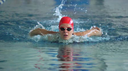 motyl : SLOW MOTION: Female athlete swims with a butterfly style. Splashes of water scatter in different directions. Wideo