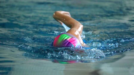 sztafeta : SLOW MOTION: Female athlete swimming in crawl style. Splashes of water scatter in different directions.