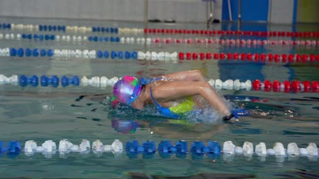 sztafeta : SLOW MOTION: Female athlete swims with a butterfly style. Splashes of water scatter in different directions. Wideo