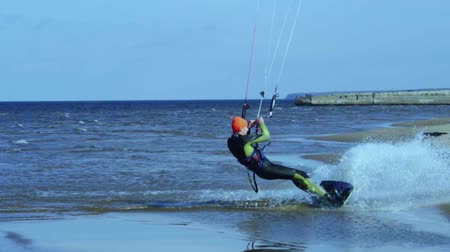 kitesurfer : SLOW MOTION: Kite surfer comes to shore from the water. Close-up. Stock Footage