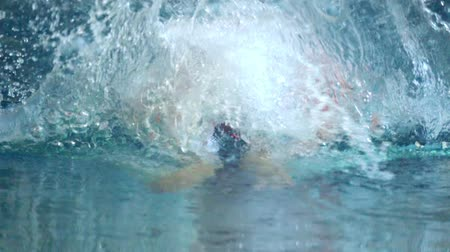 stroke : SLOW MOTION: Female athlete swims with a butterfly style. Splashes of water scatter in different directions. Stock mozgókép
