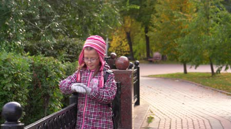 after school : Girl child walks along the path along a beautiful iron fence. A girl walks in the park after school. Autumn day.