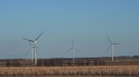 udržitelnost : Spring landscape - wind power plants, fields with dry grass, bare trees, horizon.