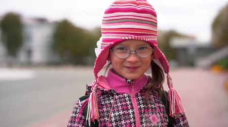 rack focus : Portrait of a smiling girl in glasses and knitted red hat. Cloudy autumn day.