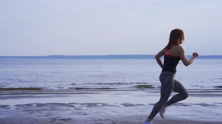 средний возраст : SLOW MOTION: Slender middle-aged woman in summer morning. Morning sports run.