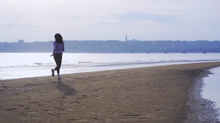 white sand : SLOW MOTION She is practicing jumping while running. Morning sports run. Stock Footage