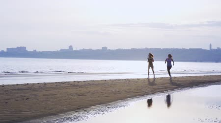 средний возраст : SLOW MOTION: Two women are jogging along a large river. Women do gymnastics in the summer morning.