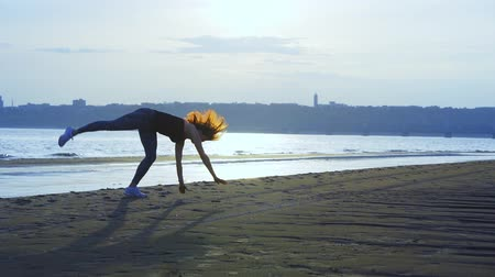 средний возраст : SLOW MOTION: A woman practices gymnastics on the sandy shore of a large river. Sunny summer morning.