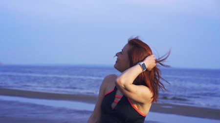 átlagos : Portrait of a red-haired middle-aged woman in sportswear. A woman walks along the sandy bank of a large river after playing sports. Close-up.