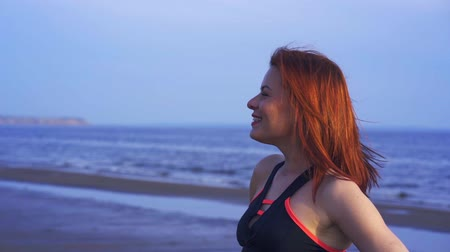 средний возраст : Portrait of a red-haired middle-aged woman in sportswear. A woman walks along the sandy bank of a large river after playing sports. Close-up.