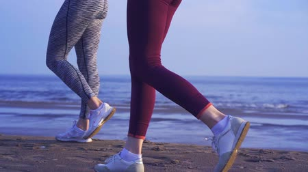 есть : There are two women in sportswear and sneakers. Sunny summer morning. Video of womens legs.