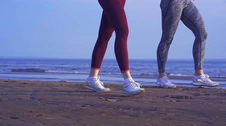 средний возраст : There are two women in sportswear and sneakers. Sunny summer morning. Video of womens legs.