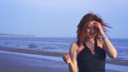 átlagos : Portrait of a laughing middle-aged woman with red hair and in sportswear. A woman walks along the sandy shore of a large river. Close-up. Stock mozgókép