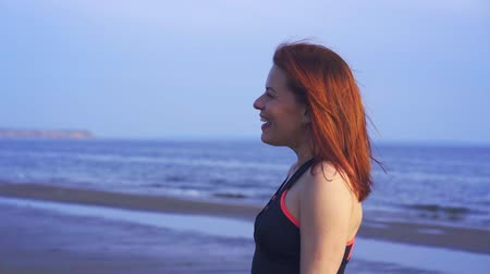 средний возраст : Portrait of a laughing middle-aged woman with red hair and in sportswear. A woman walks along the sandy shore of a large river. Close-up. Стоковые видеозаписи