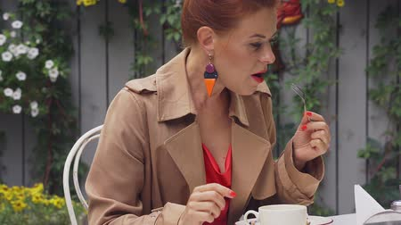 средний возраст : Red-haired pretty middle-aged woman in a brown coat sits at a street cafe, relaxes, eats dessert and drinks coffee. Cloudy summer evening. Close-up.