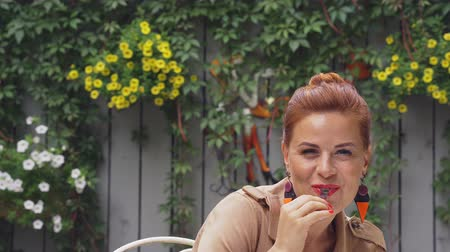 meia idade : A red-haired pretty middle-aged woman in a brown coat sits at a street cafe, rests, eats dessert and drinks coffee, laughs and talks. Cloudy summer evening. Close-up.