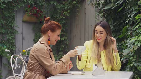 средний возраст : A middle-aged red-haired woman in a brown coat and a brown-haired young woman in a yellow coat are sitting in a summer street cafe, chatting with each other and drinking coffee. Close-up.