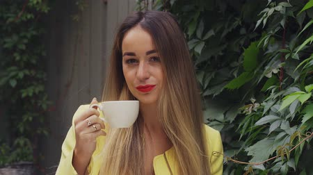 oval : A young pretty woman with long brown hair and a yellow coat is sitting in a street cafe, smiling and drinking coffee. Cloudy summer evening. Close-up.
