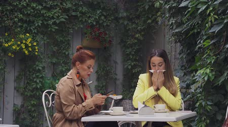 средний возраст : A middle-aged red-haired woman in a brown coat and a brown-haired young woman in a yellow coat are sitting in a summer street cafe and chatting and watching messages over the phone. Close-up. Стоковые видеозаписи