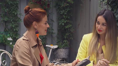 средний возраст : A middle-aged red-haired woman in a brown coat and a brown-haired young woman in a yellow coat are sitting in a summer street cafe and choosing what to order. Close-up. Стоковые видеозаписи