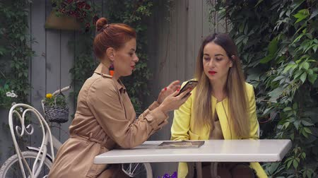 oval : A middle-aged red-haired woman in a brown coat and a brown-haired young woman in a yellow coat are sitting in a summer street cafe, talking and showing photos on the phone. Close-up.