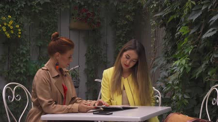 oval : A middle-aged red-haired woman in a brown coat and a brown-haired young woman in a yellow coat are sitting in a summer street cafe, chatting and choosing what to order. Close-up.