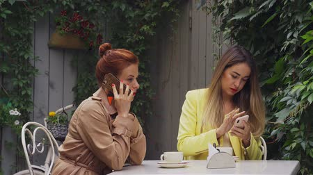 средний возраст : A middle-aged red-haired woman in a brown coat and a brown-haired young woman in a yellow coat are sitting in a summer street cafe and communicate by phone. Close-up. Стоковые видеозаписи