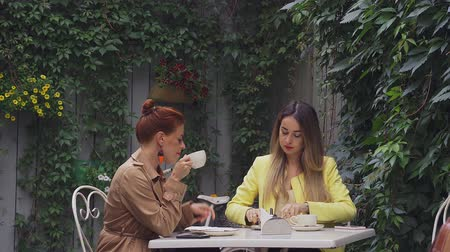 meia idade : A middle-aged red-haired woman in a brown coat and a brown-haired young woman in a yellow coat are sitting in a summer street cafe and eating dessert and drink coffee. Close-up.