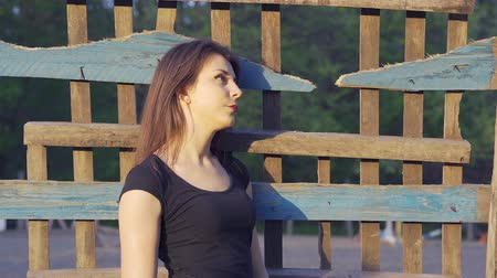 avelã : Portrait of a young country woman with dark brown hair and in a black T-shirt, shot in the countryside. Close-up. Sunset. Stock Footage