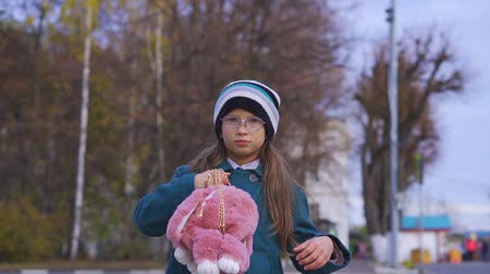 knitted : Portrait of teenage girl with glasses, in a dark turquoise coat, in a knitted hat and a pink bag with a backpack in the form of a soft toy. Autumn day. Stock Footage