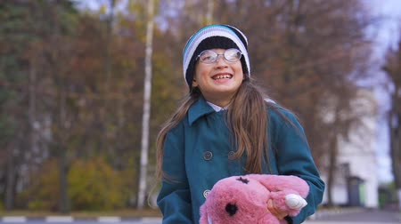 Portrait of a laughing teenage girl with glasses, in a dark turquoise coat, in a knitted hat and a pink bag with a backpack in the form of a soft toy. The girl enjoys the new backpack. Autumn day.