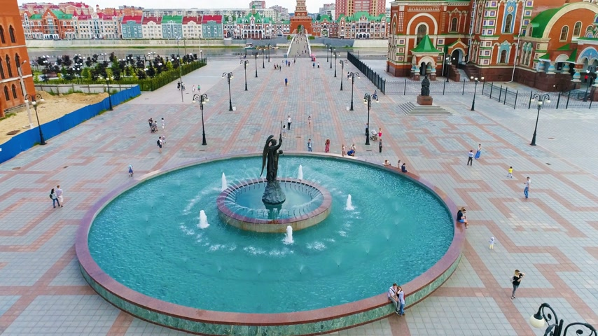paus : Turquoise Fountain in the city square in summer sunny day near the church - Drone Footage