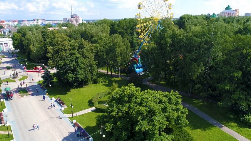 fade in : City square in the green park with ferris wheel in summer warm cloudly day. People are walking serenely - Drone Footage