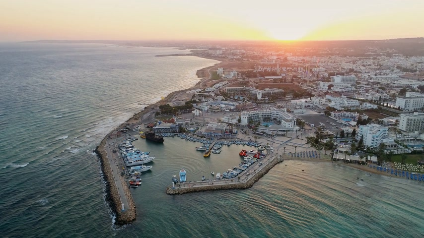 turné : Drone Flying Away From a Pier in Summer Sunset. Beautiful Seaside City with Parks and Hotels - Cyprus Stock mozgókép