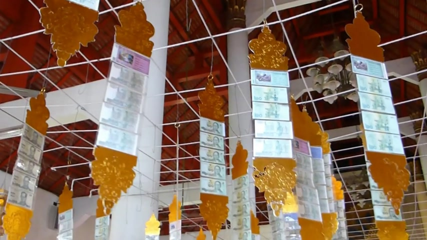 budist : Temple donation money hanging on metal trellis in a Thai temple, Chiangmai.  Thai people are never out of money regarding donations to Buddhist temples.  Stok Video