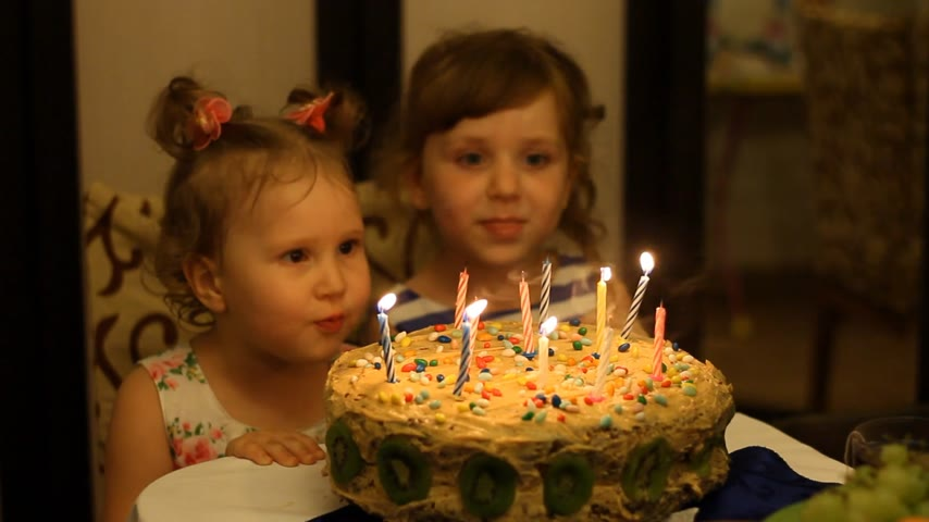 darbe : Little girls blows out candles on birthday cake at party
