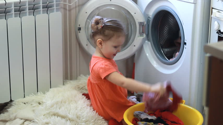 çamaşırhane : Funny cute little girl gets clean things from the washing machine. Baby and laundry.