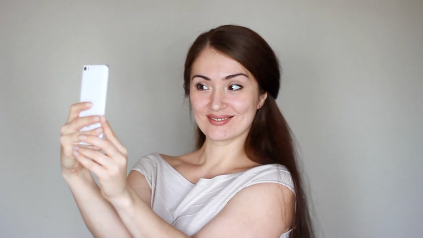 škádlení : Young woman taking photo or making selfie on your phone or smartphone. Funny girl smiles and banter.