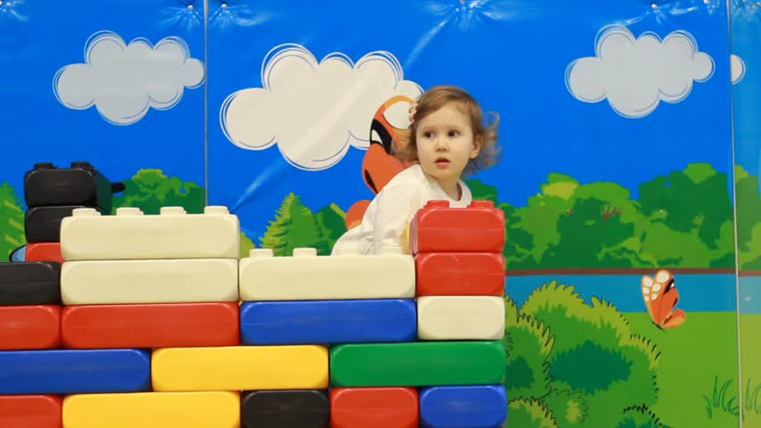 preschool : Funny cute child on the playground plays different games and and collects the constructor. Little girl and entertainment and development of preschool children Stock Footage