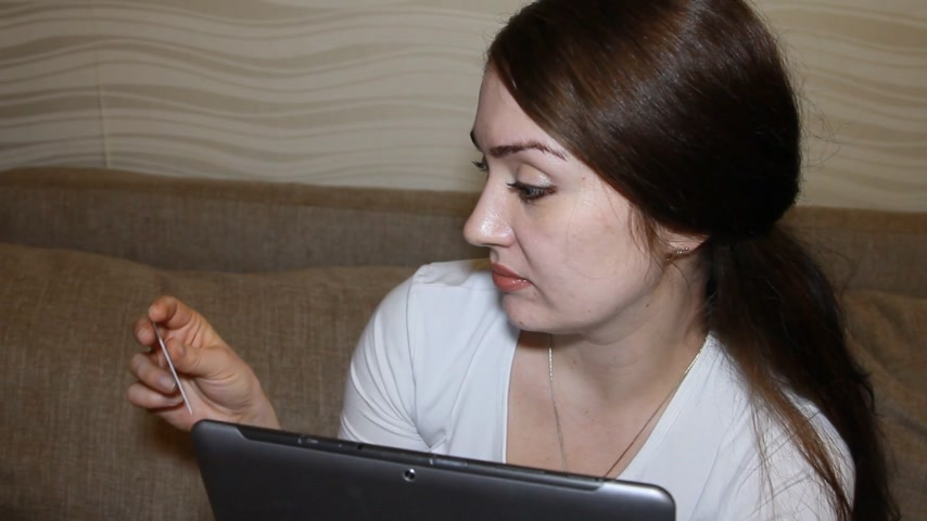jegyzettömb : Beautiful young woman online banking using tablet computer shopping online with credit card at home lifestyle Stock mozgókép